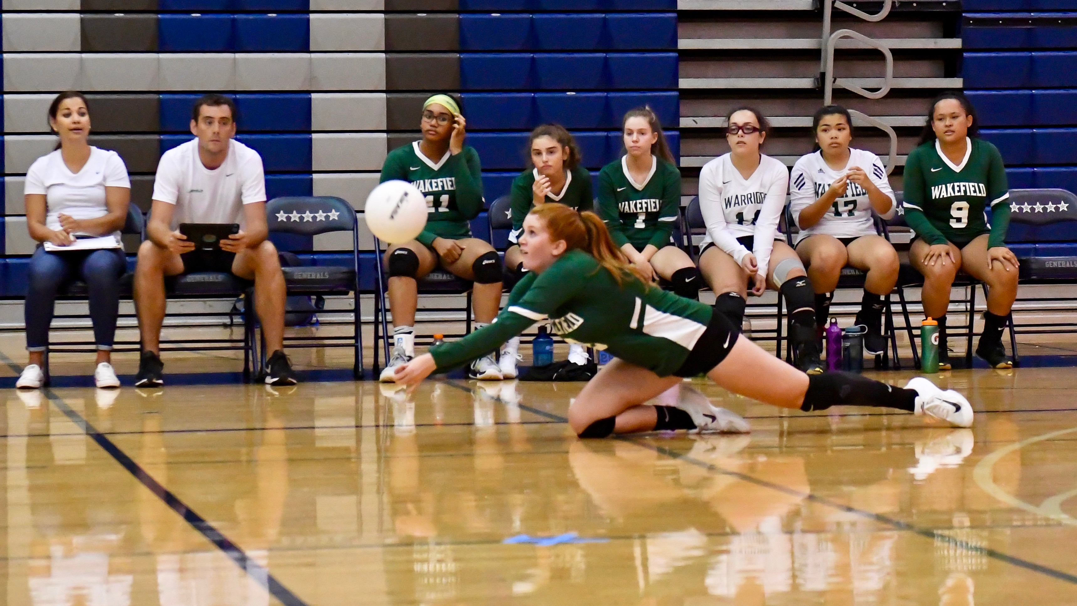 Volleyball player dives for the ball
